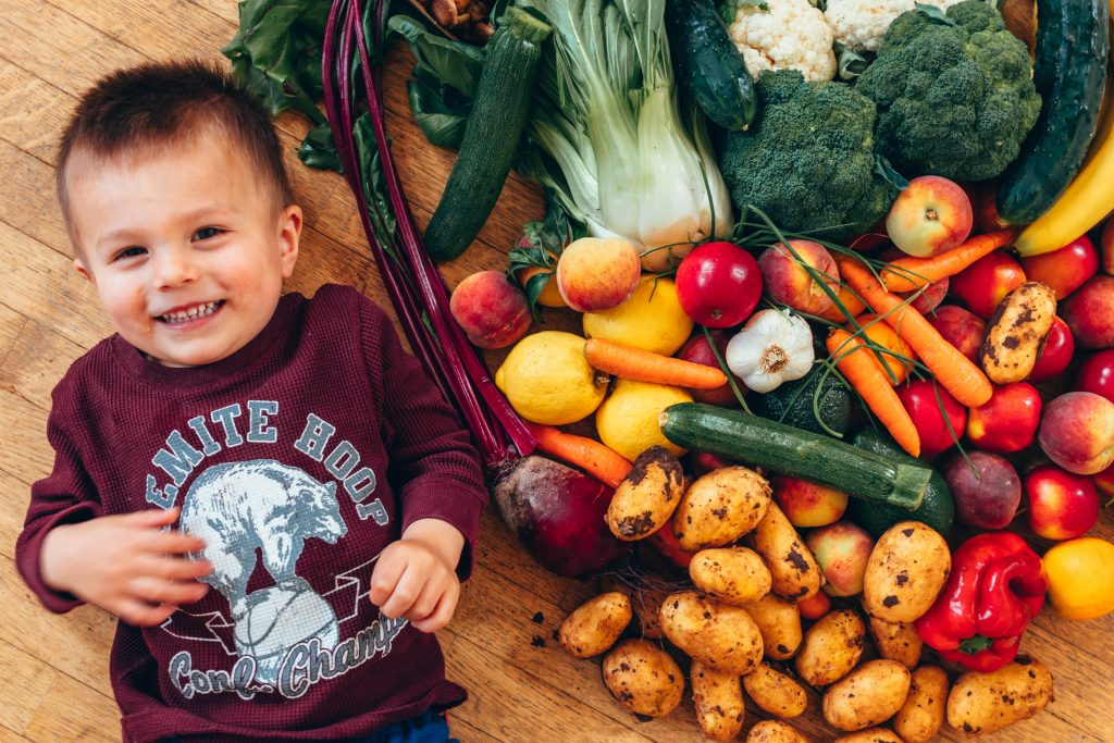 child sitting with fruits and vegetables