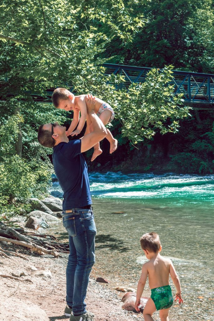 Father and Sons at the river playing